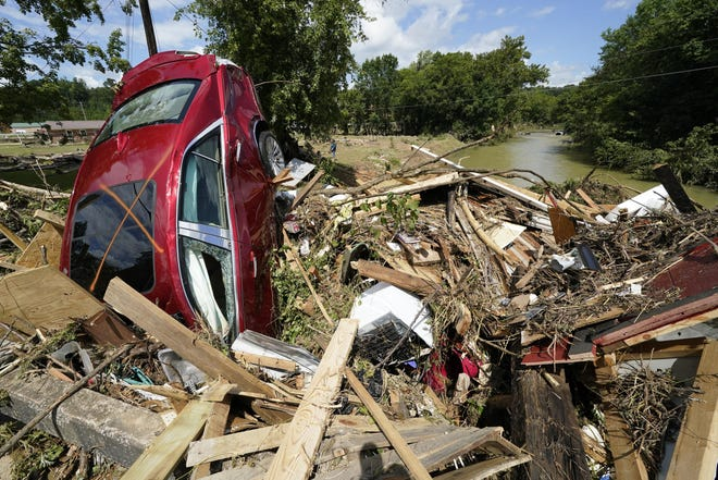 A car is among debris that washed up against a bridge over a stream Sunday, Aug. 22, 2021, in Waverly, Tenn. Heavy rains caused flooding Saturday in Middle Tennessee and have resulted in multiple deaths as homes and rural roads were washed away. (AP Photo/Mark Humphrey)