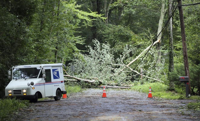 A U.S. Postal truck has to turn around as Gardner Rd. in Exeter, R.I., is completely blocked by a downed tree and power lines, Monday, Aug. 23, 2021. Strong winds from Tropical Storm Henri downed trees and power lines across the state leaving roads impassable and citizens without power. (AP Photo/Stew Milne)