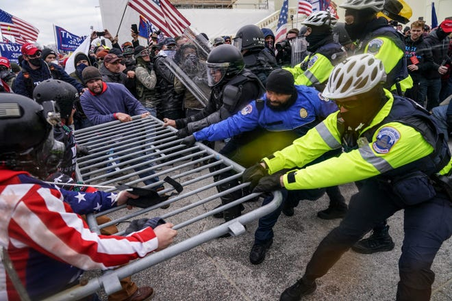 Insurrectionists loyal to President Donald Trump try to break through a police barrier at the Capitol in Washington on Jan. 6, 2021.