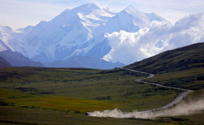 A tour bus kicks up dust during a sunny day at Denali National Park in Alaska.