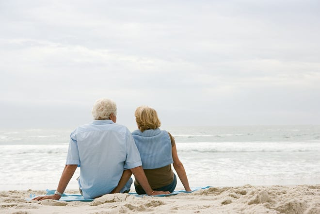 Two people sitting on the beach together.
