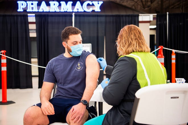 Ben Arnett, left, watches as his arm is prepared for his second dose of the COVID-19 vaccine at the Knox County Health Department vaccine center in Knoxville, Tennessee, on April 5.