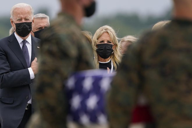 President Joe Biden and first lady Jill Biden stand with their hands over their hearts as a carry team moves a transfer case with the remains of Marine Corps Cpl. Humberto A. Sanchez, 22, of Logansport, Indiana, during a casualty return at Dover Air Force Base in Delaware on Sunday for the 13 service members killed in the suicide bombing Thursday in Kabul, Afghanistan.