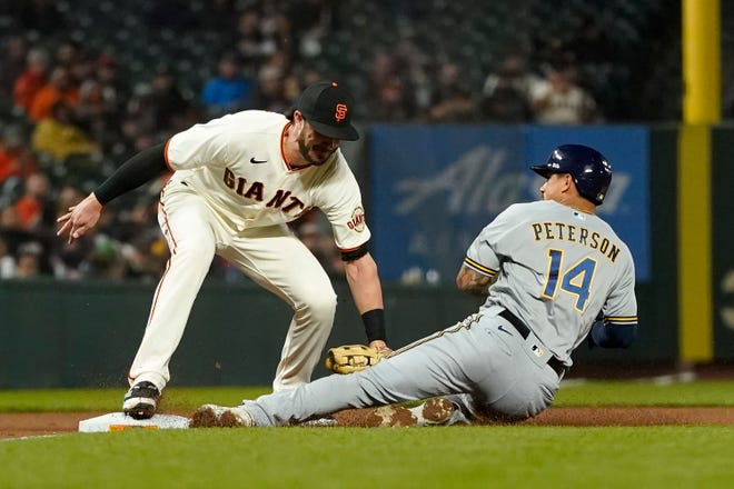 Milwaukee Brewers' Jace Peterson is tagged out by San Francisco Giants third baseman Kris Bryant while trying to steal third during the fourth inning Monday. Bryant was traded from the Chicago Cubs to the Giants in July.