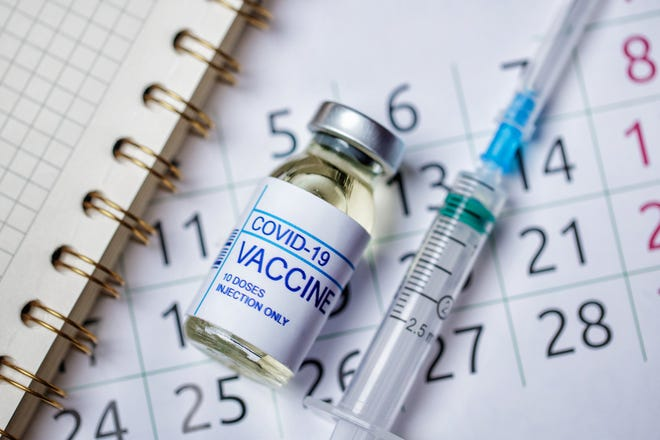 COVID-19 vaccine vial and syringe on top of a calendar.