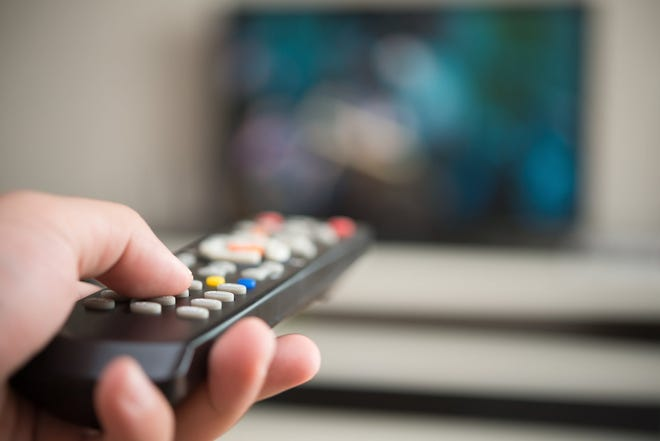 A hand points a remote at a distant and blurred TV set.