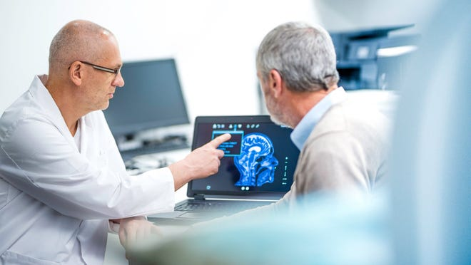 A neurologist shows a patient an image of his brain scan.