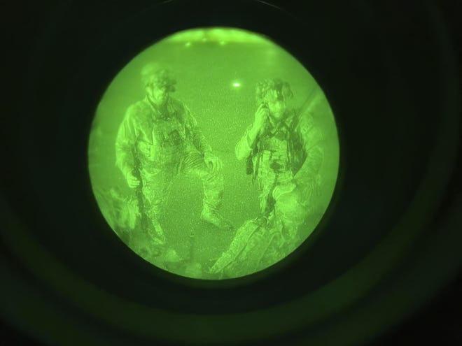 In this image made through a night vision scope and provided by the U.S. Army, Maj. Gen. Chris Donahue, commander of the U.S. Army 82nd Airborne Division, XVIII Airborne Corps, prepares to board a C-17 cargo plane at Hamid Karzai International Airport in Kabul, Afghanistan, Monday, Aug. 30, 2021, as the final American service member to depart Afghanistan. (Master Sgt. Alexander Burnett/U.S. Army via AP)