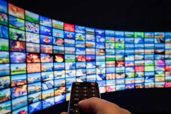 A hand points a remote control at a huge wall of TV screens, all showing different content.