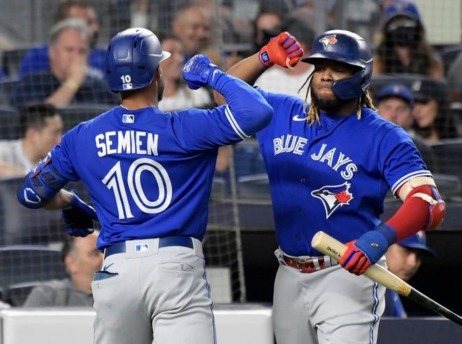 Marcus Semien (10) de los Blue Jays de Toronto celebra con Vladimir Guerrero Jr. luego de que Semien conectó un jonrón contra los Yankees de Nueva York durante la quinta entrada de un juego de béisbol el martes 7 de septiembre de 2021 en el Yankee Stadium de Nueva York.  (Foto AP / Bill Kostroun)
