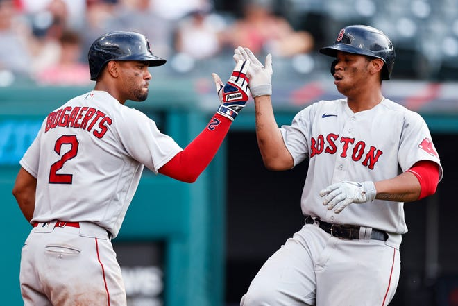 Boston Red Sox's Rafael Devers celebrates with Xander Bogaerts (2) after hitting a solo home run against the Cleveland Indians during the seventh inning of a baseball game, Sunday, Aug. 29, 2021, in Cleveland. (AP Photo/Ron Schwane)