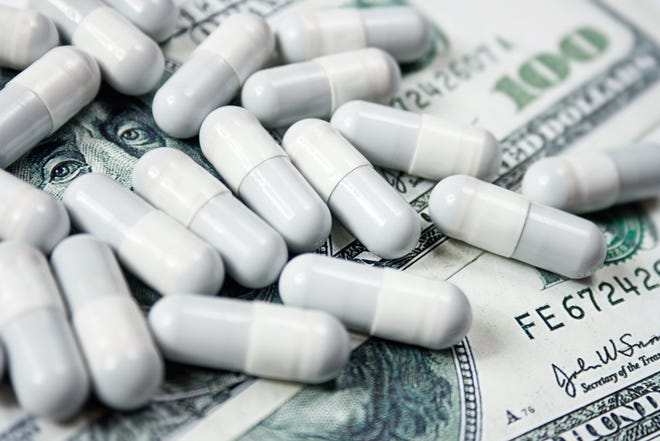 A handful of prescription drug capsules set atop a fanned pile of one hundred dollar bills.
