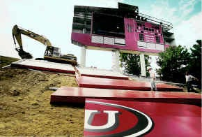 Randy Stevens, left, and Paul Bredeweg work under a new Indiana University scoreboard being installed at Memorial Stadium on Friday. The scoreboard may be ready for the season opener against Ball State today. Staff photo by Jeremy Hogan