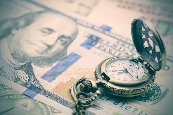 Pocket watch sitting on $100 bills
