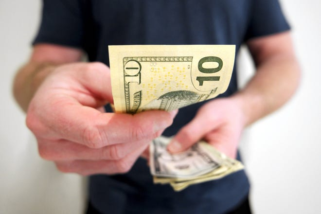Person handing over a $10 bill.