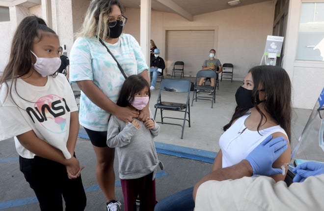 Left to right, Alana Alfaro, 9, and her mother Tracie Alfaro, holding Penelope Alfaro, 6, watch their sister Juliet Alfaro, 13, get vaccinated at the Rio Mesa High School pop-up vaccination clinic Sept. 2 in Oxnard, California.