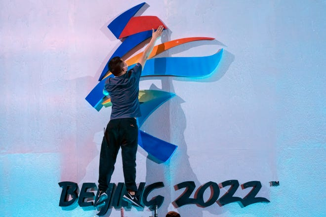 A crew member leaps to fix a logo for the 2022 Beijing Winter Olympics.