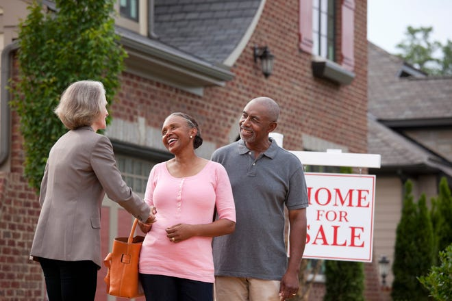 A real estate agent standing with their clients outside their home, preparing to list it for sale.