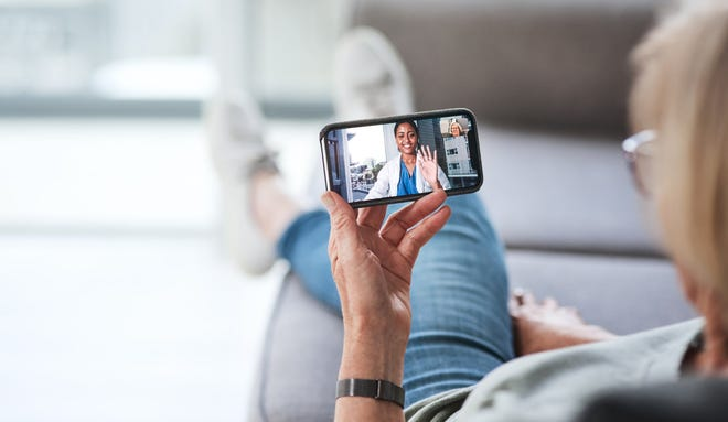 A person holding a smartphone showing a healthcare professional on the screen.