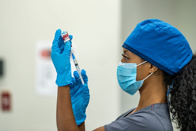 A healthcare professional holding a syringe and needle up to a vaccine vial.