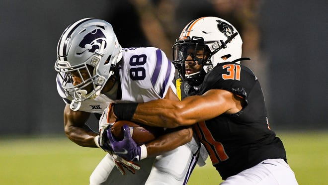 Kansas State receiver Phillip Brooks (88) is tackled by Oklahoma State safety Kolby Harvell-Peel (31) on Saturday in Stillwater, Okla.