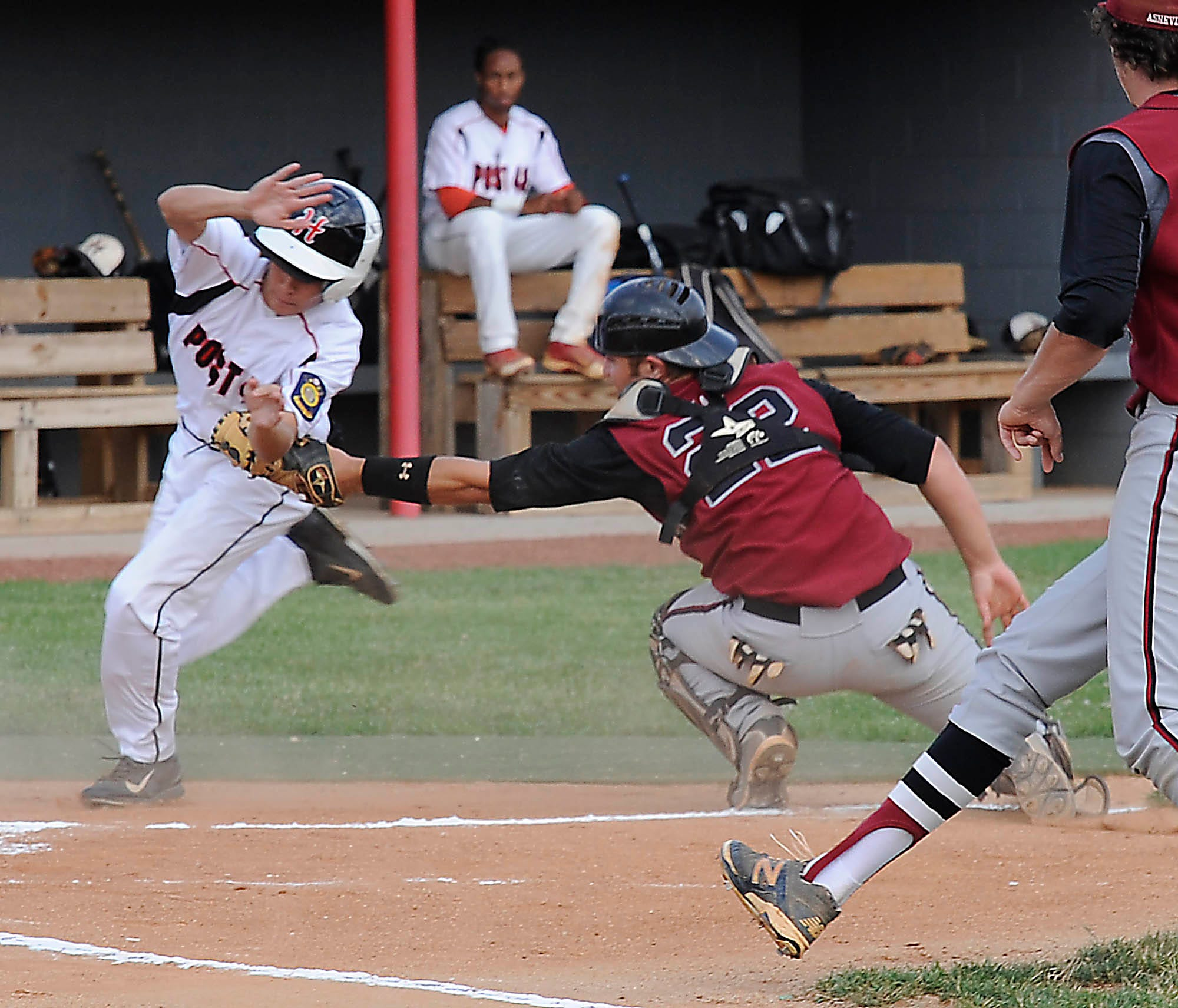 Asheville Post 70 catcher Tanner Smith tries to apply a tag to a Hickory Post 48 baserunner in Monday night's playoff game at Erwin High.