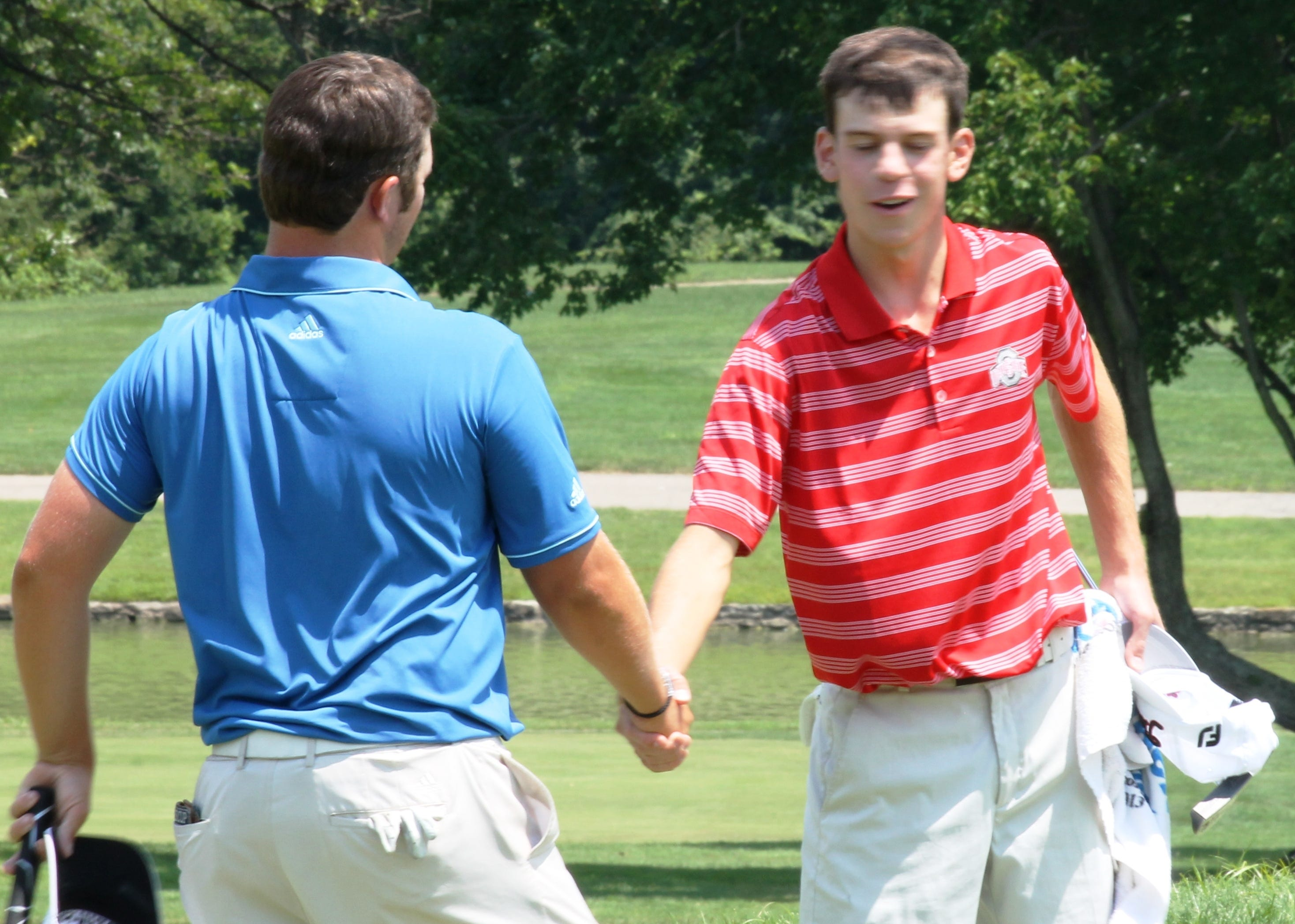 Ohio Amateur golf champion Andrew Dorn, left, shakes hands with runner-up Will Grimmer July 11 on the 18th green at Coldstream Country Club. Dorn needed a closing round of 66, five under par, to edge Grimmer 276-277 by one stroke in the four-day tournament.