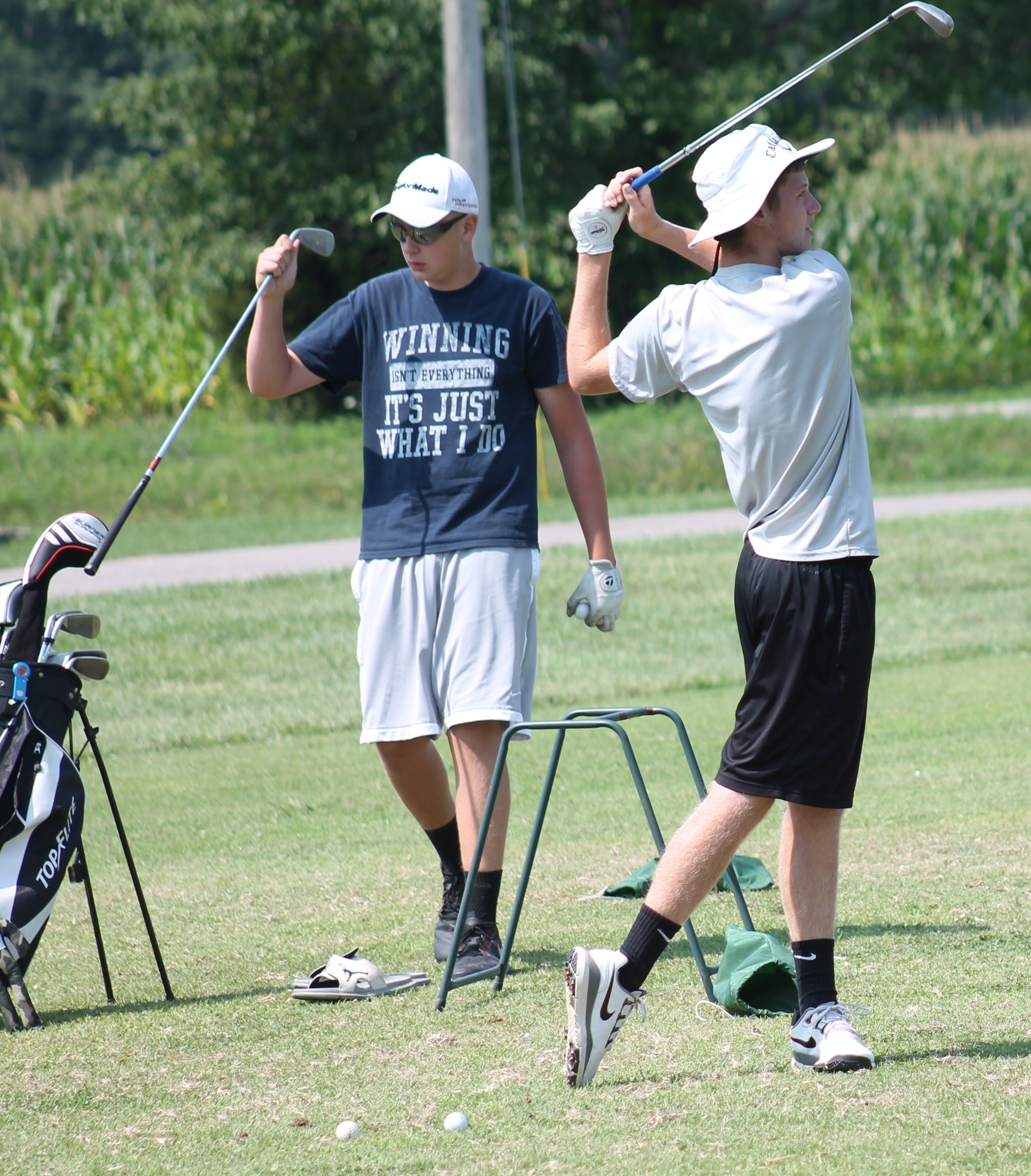 Bethel-Tate juniors Mitchell McElfresh (swinging) and Blake Combs get some work in on the range at Friendly Meadows Aug. 1.