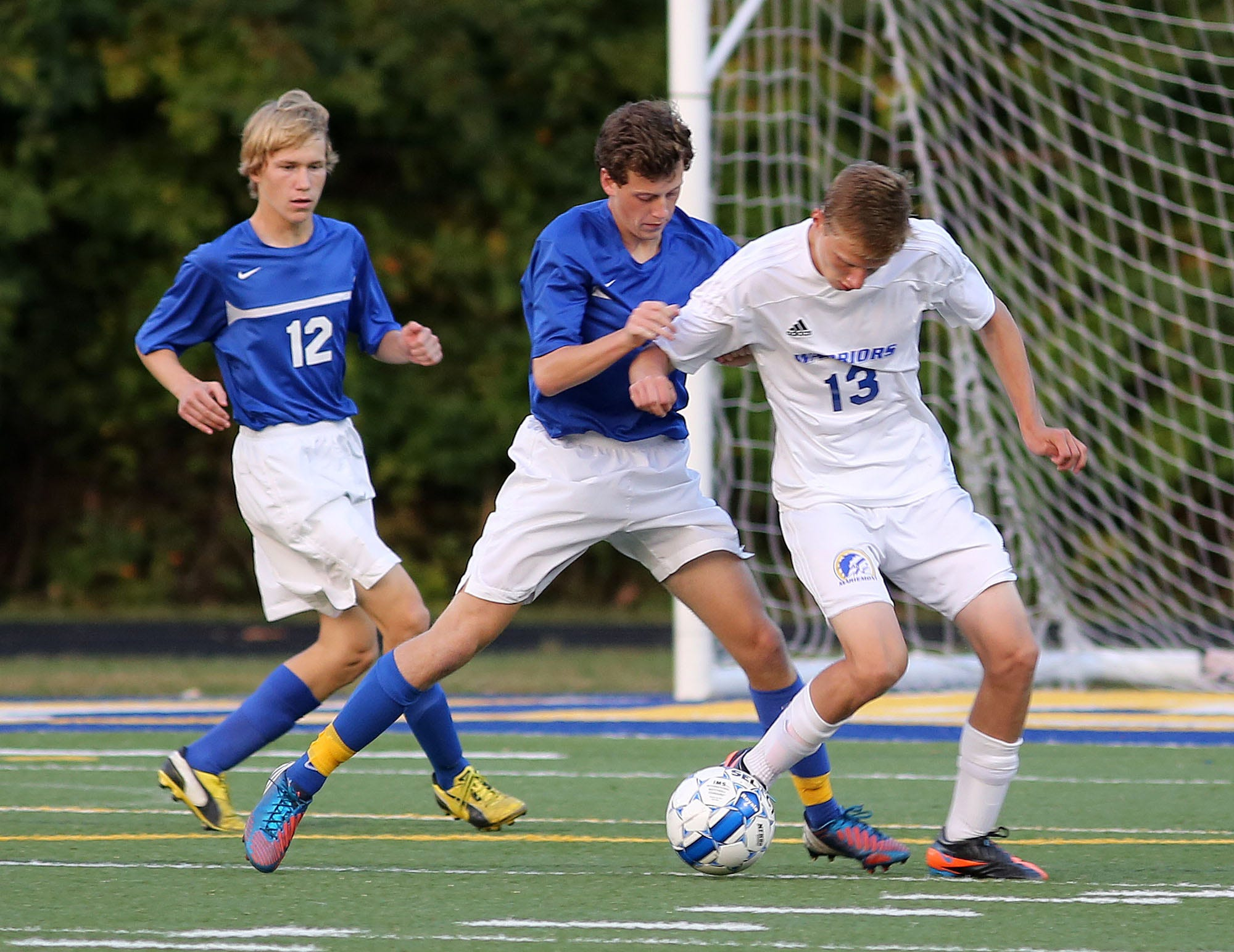 Madeira's Eric Cummings (12) and Preston Kahn team up on Mariemont's Sander Henning last October. Cummings is back for the Mustangs as a sophomore defender.