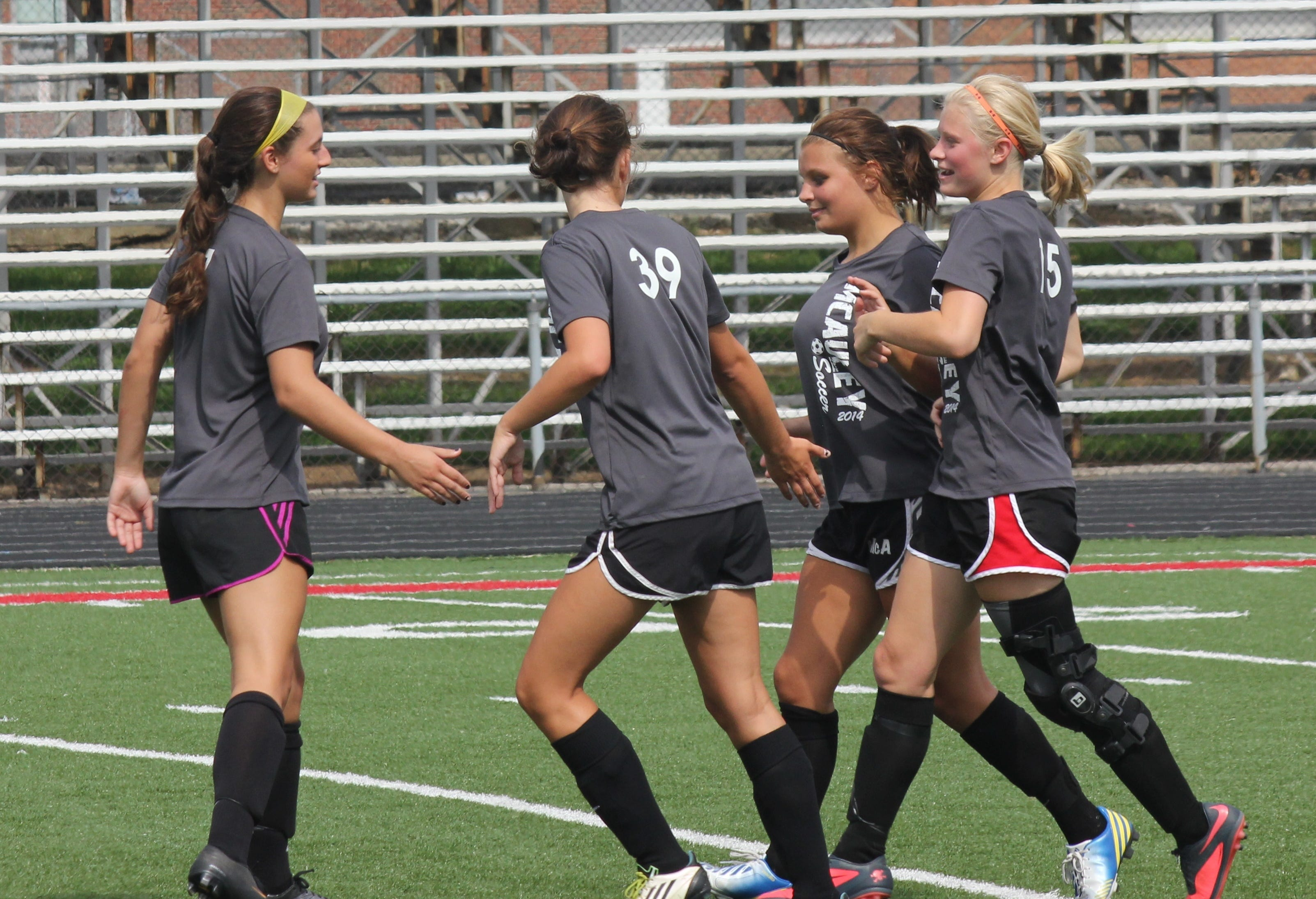 The McAuley players congratulate Sam Petri for scoring during a scrimmage against Badin in a 1-1 tie July 12 at Fairfield. The junior is back after missing her sophomore year with injuries to both her knees.