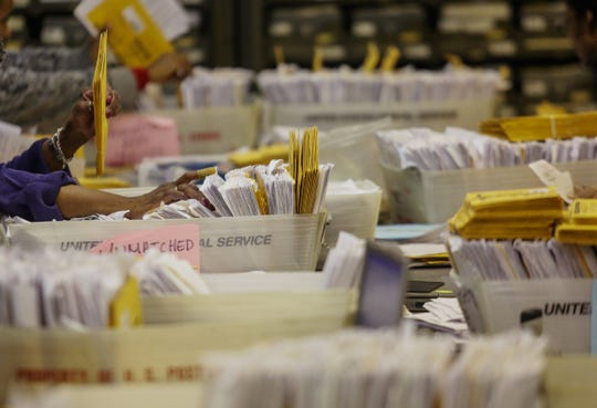 Workers sort through stacks of unmatched ballots while matching them with applications as they prepare absentee ballots returned on Wednesday, Oct. 29, 2014, at the City of Detroit Department of Elections in Detroit before being able to count them on Election Day.