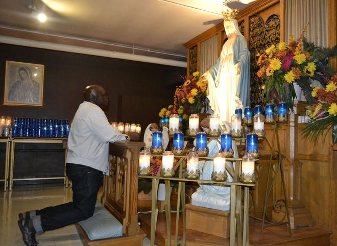 The Rev. Ubald Rugirangoga prays as he kneels Wednesday in front of a statue of Our Lady of Grace in the crypt at The Shrine of Our Lady of Good Help in Champion. Rugirangoga, a well-traveled Roman Catholic priest from Rwanda, has given a handful of Masses at the popular shrine in his tours of the United States since 2009.