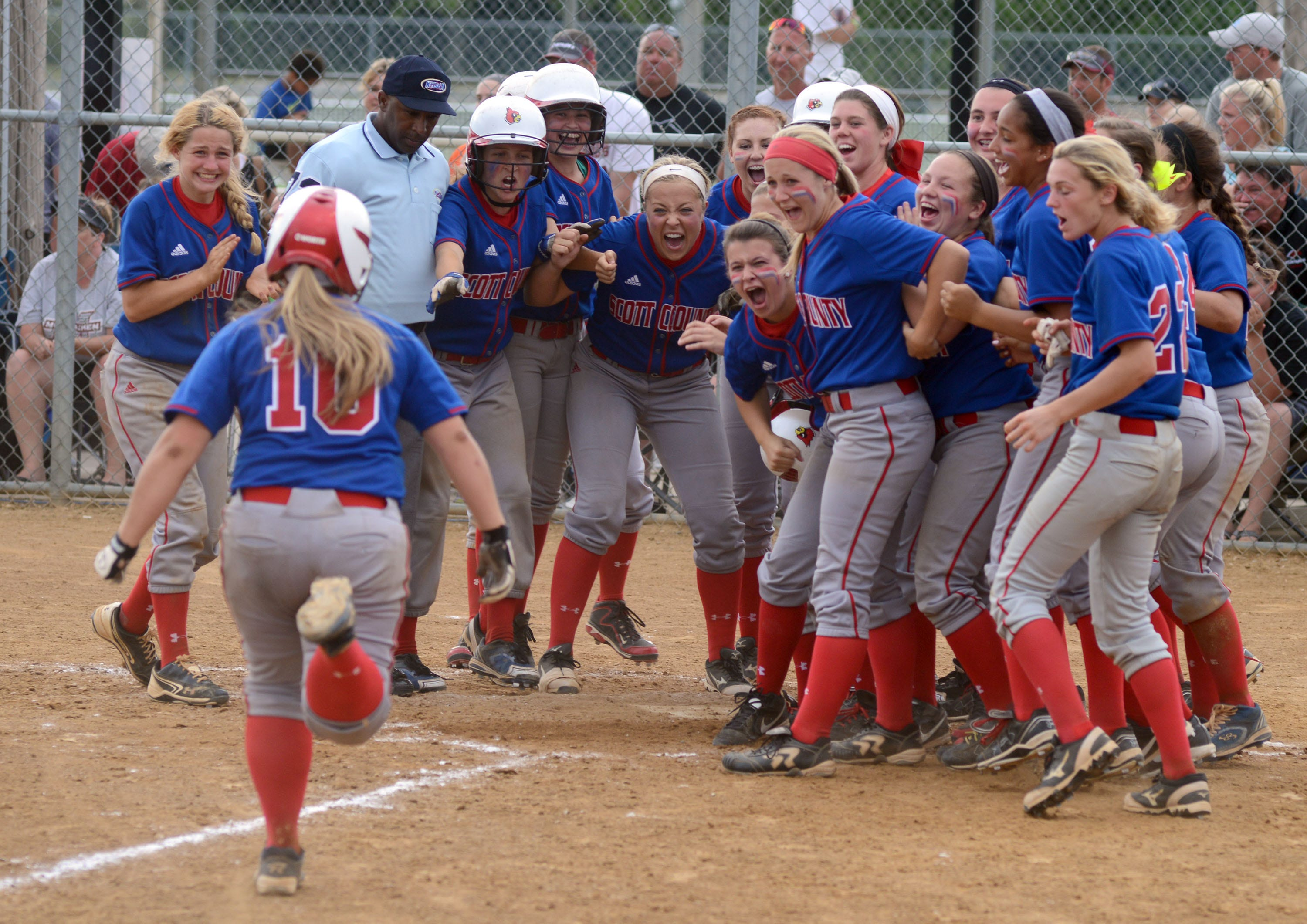 Taylor Ricketts comes home to a celebration after the first grand slam of her career gives Scott County a 6-2 lead Saturday. It was a happier moment for Ricketts, who committed three errors in an 11-1 loss in the first game against McCracken County.