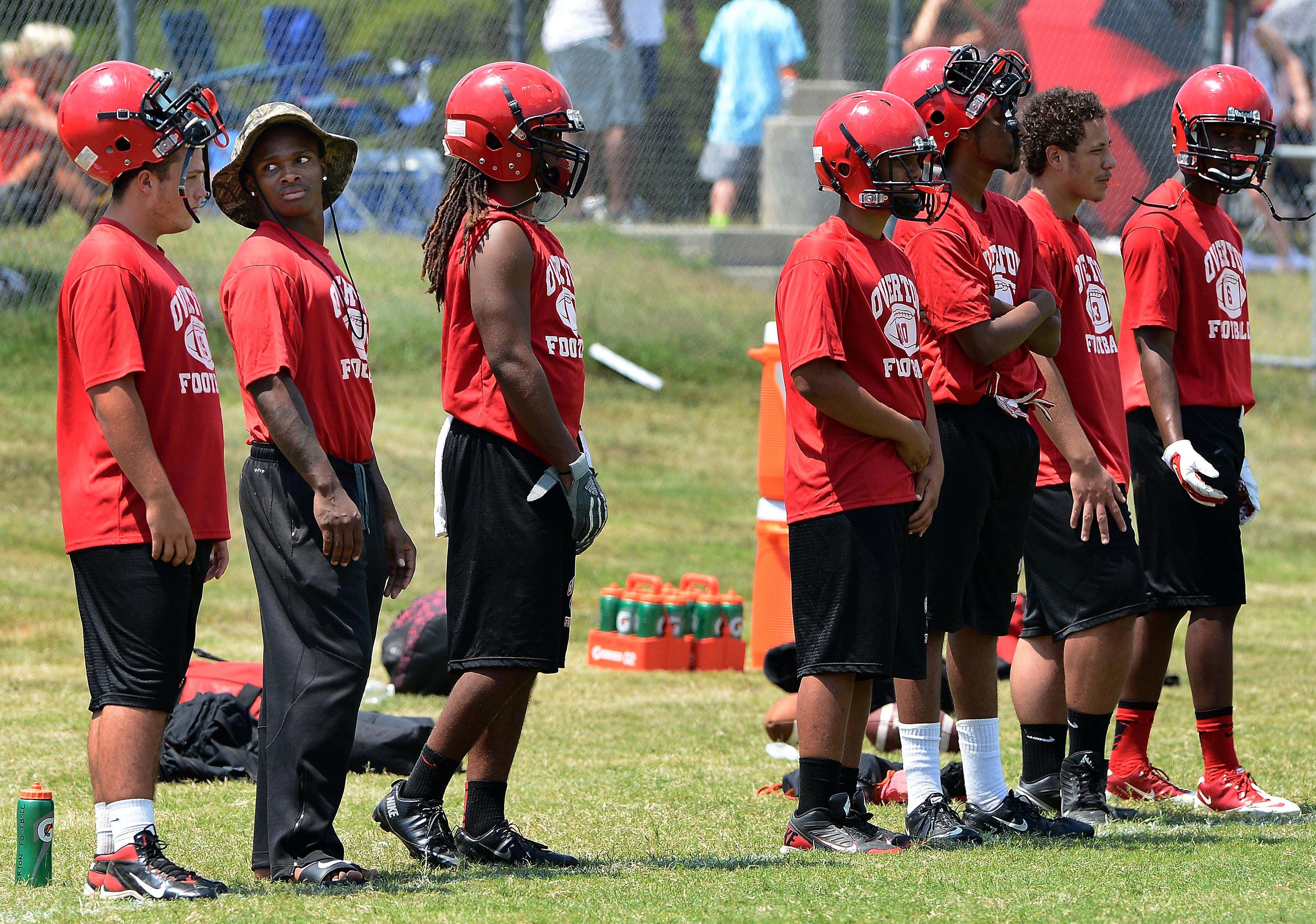 Overton High school running back Nick Fuqua, second from left, watches from the sidelines during the 7-on-7 passing league tournament at Ravenwood High School Saturday.
