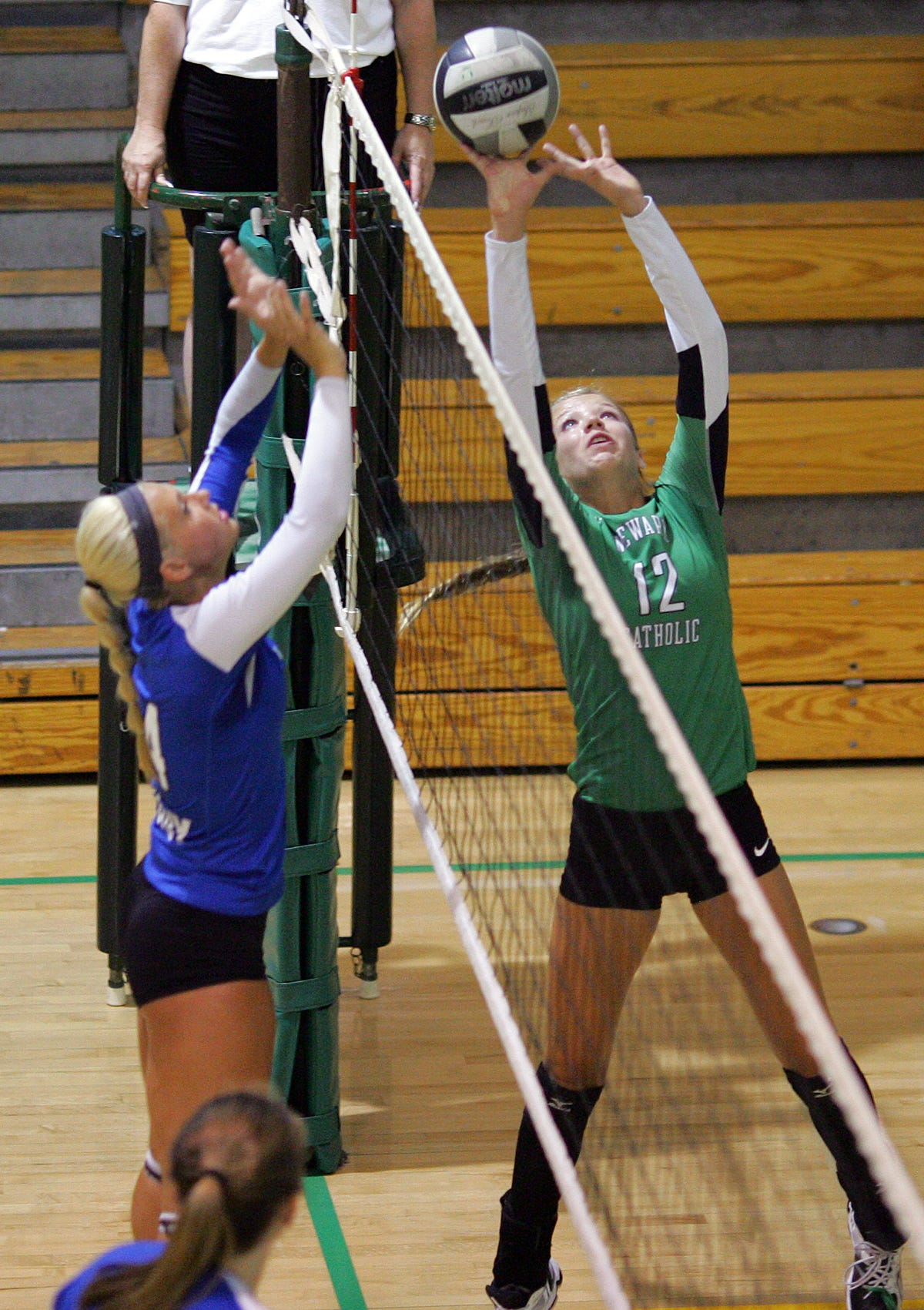 Newark Catholic's Megan Stanton tips the ball over the net Friday against Bishop Ready during the Newark Catholic Preview.