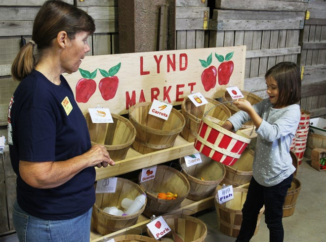 """Lynd Fruit Farm offers school tours, which teach youngsters about how food gets from a farm to their local grocery store. Here, Beth Styers, of Lynd Fruit Farm, helps Granville resident May Drew, 7, along the so-called """"Lil Farmer Tour."""""""