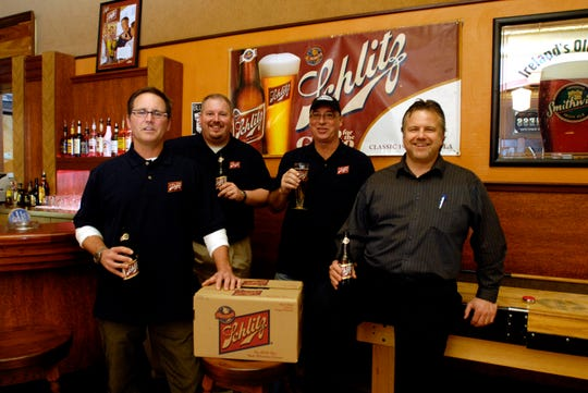 Owners of Oblio's Mark Shultz (glasses) and Todd Cummings (hat) welcome the return of Schlitz Beer in 2009.