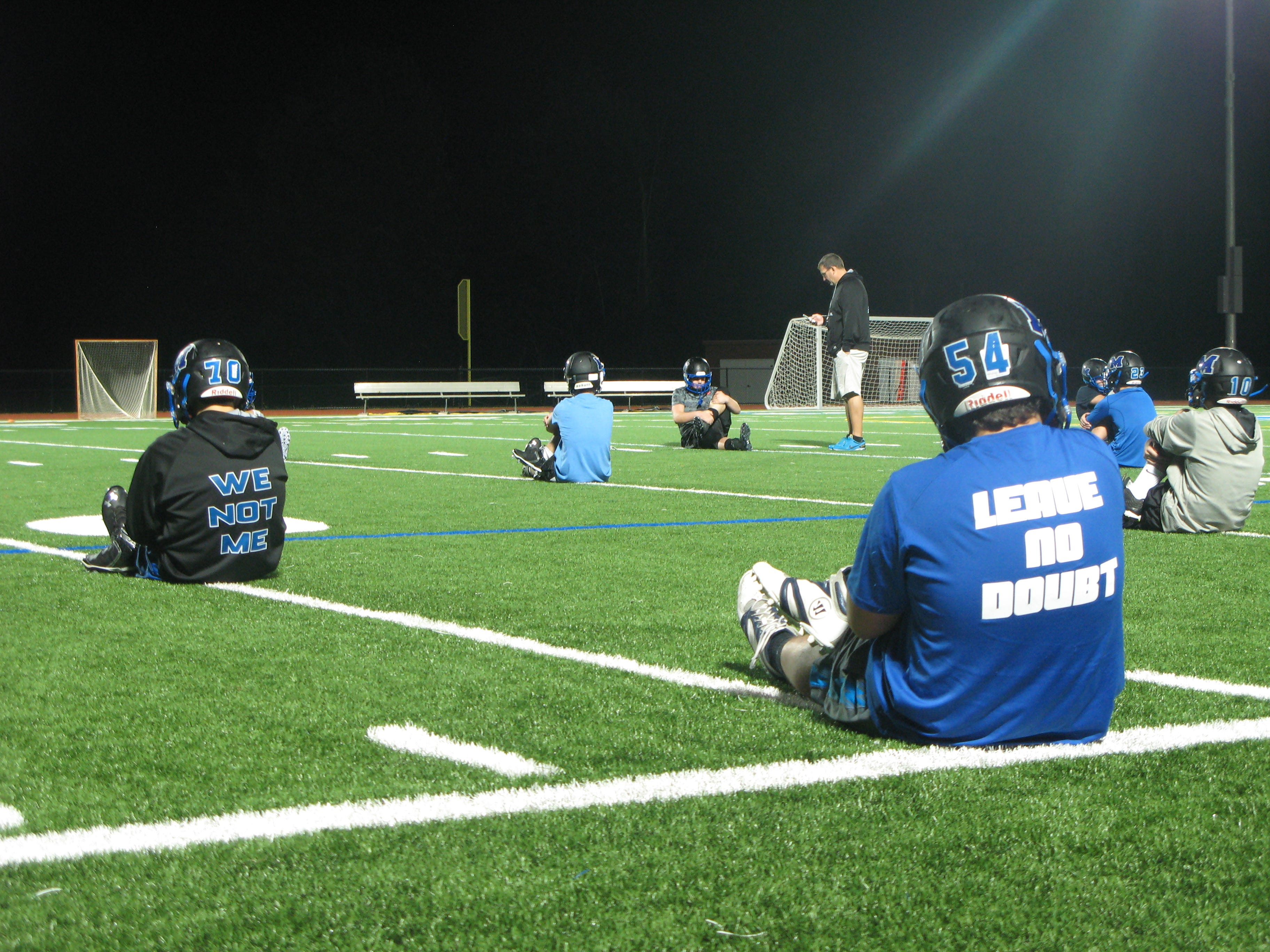 """The Millbrook High School football team, wearing team gear with phrases like """"We Not Me"""" and """"Leave No Doubt"""" stretches before practice early Monday morning."""