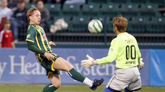 Rochester's Tam McManus, left, chips a shot over a charging VSI Tampa Bay goalkeeper Dave Martin for a goal during USL soccer action between the VSI Tampa Bay FC and the Rochester Rhinos at Sahlen's Stadium in Rochester Friday evening, June 14, 2012. McManus finished with a goal and an assist in the Rhinos 3-0 victory.