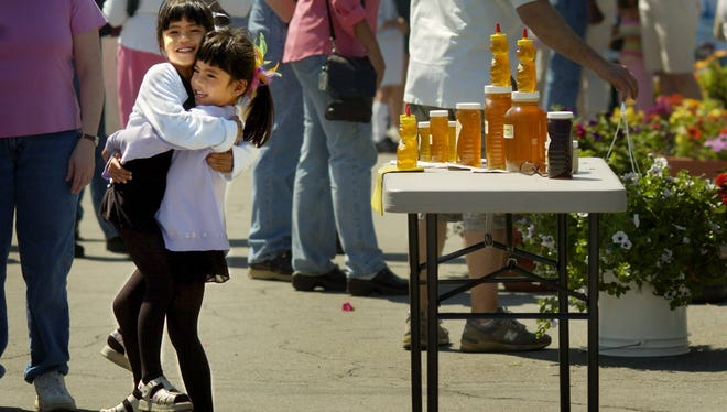 Elizabeth Priest, 5, left, gets a hug from her twin sister Hannah at the Fairport Farmers Market in 2005.