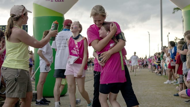 Mother and daughter team racers finish the Girls on the Run 5k race at MCC on June 1, 2013.