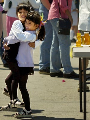 Elizabeth Priest, 5, left, gets a hug from her twin sister Hannah in front of Frank Reber's honey stand at the Fairport Farmers Market in 2005