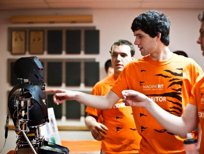 Tom Whitmore, center, of Henrietta and RIT fifth year mechanical engineer student is one of the students that worked on the TigerBotIV is a semi-autonomous humanoid robot capable of interacting with users through speech recognition. Sat., May 4, 2013. TigerBotIV looks like a Hollywood futuristic version of a humanoid robot.