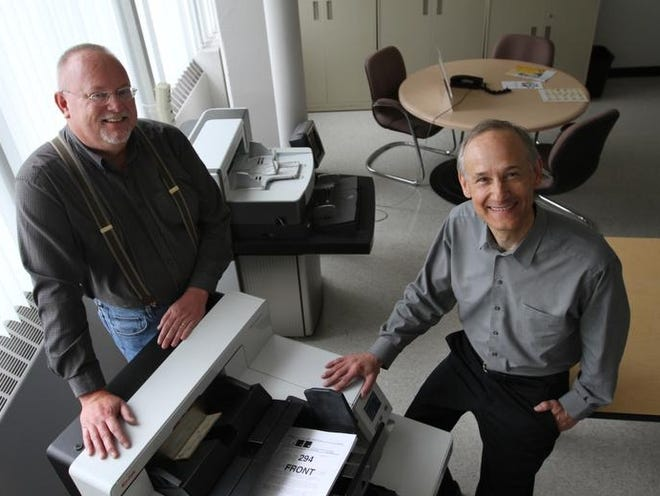 L-R  Robert Westcott, of Holley, mechanical and systems manager DI Development and Stephen Reinke of Brighton, mechanical engineer Document Imagining, both with Eastman Kodak Company, with the Kodak i5800 with controlled dual stacking accessory high speed document scanner they helped invent.  They scanner can scan different size documents such as the regular size paper and check size that is demonstrated on the scanner on June 10, 2013.