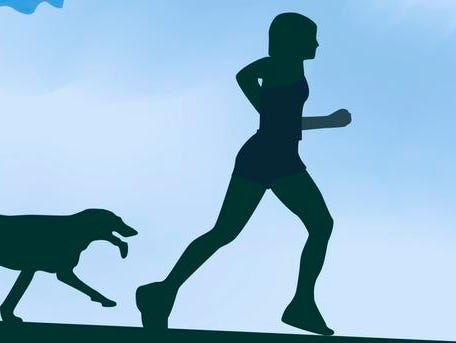 Low angle view of a man running with his dog