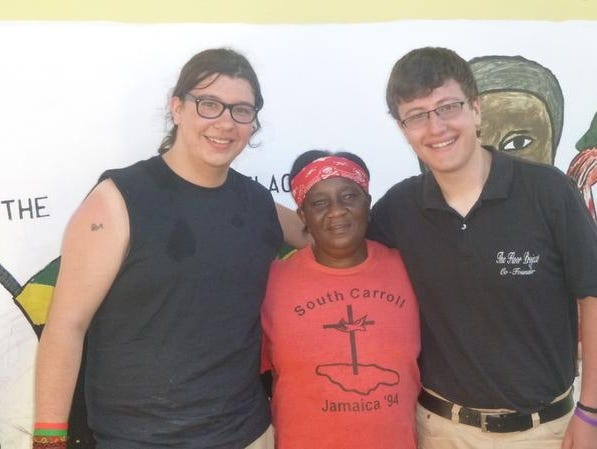 Tyler Poquette, left, and Brennon Thompson, right, with the Jamaican woman for whom they built a floor.