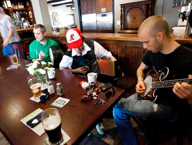(left to right) Eddie Sheridan owner of Sheridan's Pub, John M. Ryan of Penfield and Rayce Malone of Brighton play on a traditional Irish music session at Sheridan's Pub in Brighton, Sun., June 9, 2013. The ever changing group of musicians play every Sunday at 2:00 p.m as a way to enjoy the company of musicians and play music together.