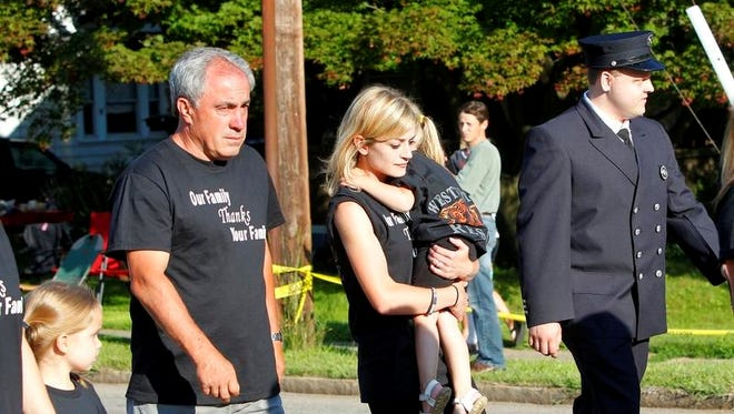 """At left, the families of Chiapperini and Kaczowka wear shirts stating """"Our Family Thanks Your Family"""" as they walk in the parade."""