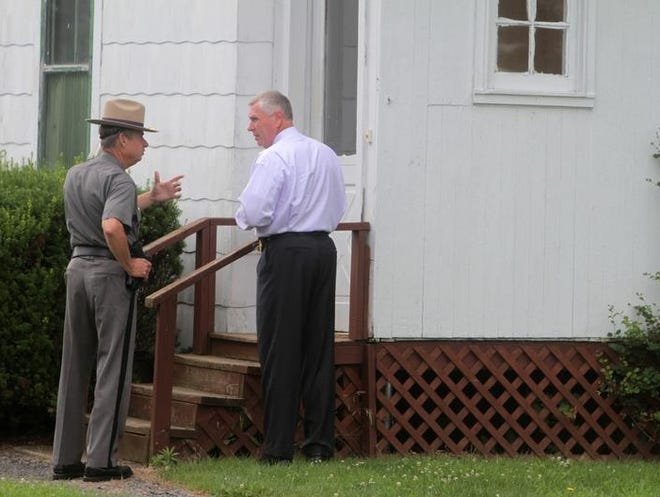 New York State Police investigate the death of Terri Moulton and her daughter, Stacey, at a neighbor's house on State Route 14 in Sodus on Monday.