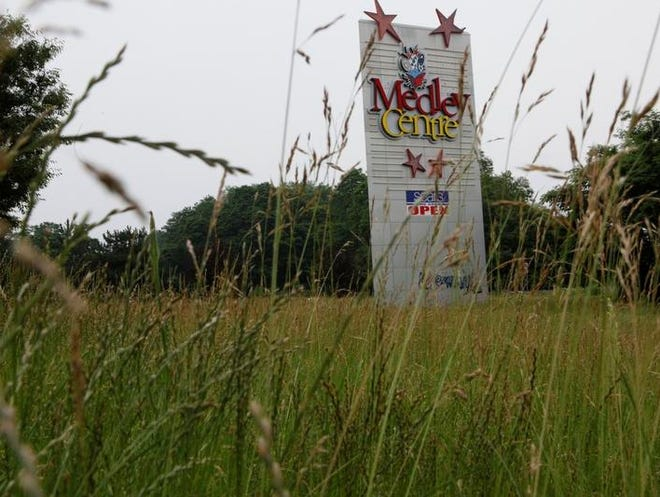 The Medley Centre sign is surrounded by tall weeds by the entrance of the vacant mall.
